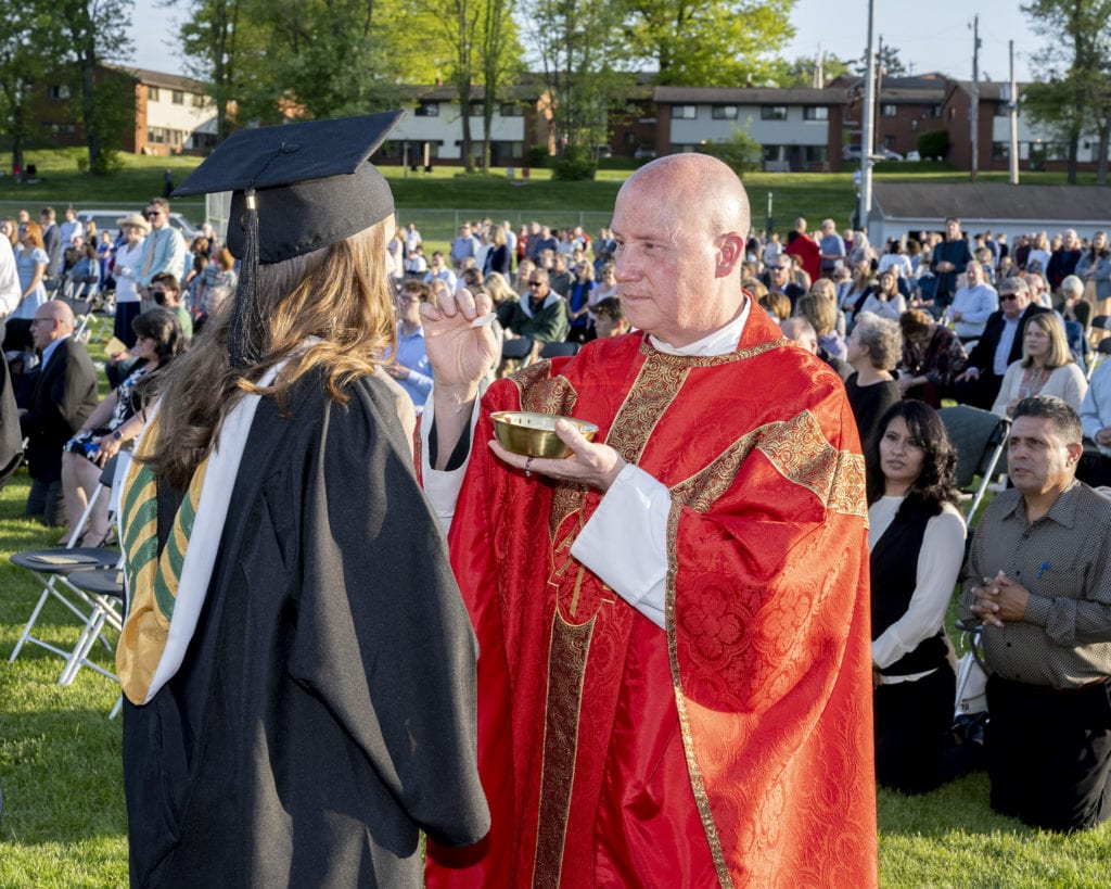 Father Dave Pivonka, TOR, distributes communion at the Baccalaureate Mass.