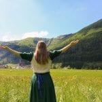 A girl stands in a field in Austria