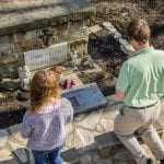two students kneeling before the tomb of the unborn child