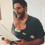 man working while holding child