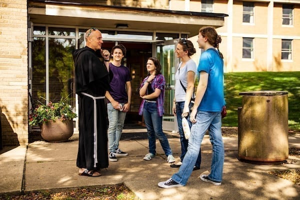 Father Dave with Students outside a dorm