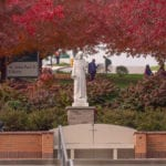 St. Francis Statue and red leaves on trees